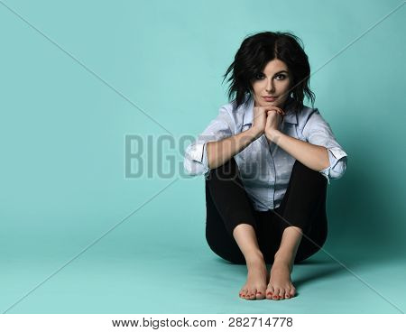 Easygoing Slight Smiling Young Woman In Light Blue Shirt Sits On The Floor And Support The Chin With