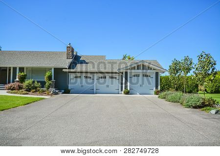 Wide Asphalt Driveway Of Residential House With Three Stall Garage Attached