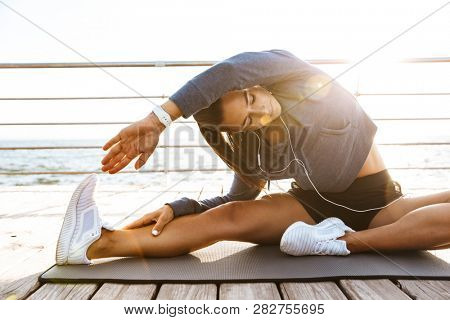 Image of a beautiful young sports fitness woman make stretching exercises at the beach outdoors listening music with earphones.