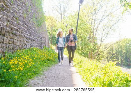 Young travelers walking in a park. Man and woman having vacation. Backpackers, traveling and tourism.