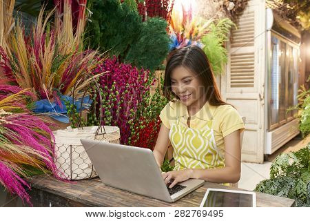 Pretty Smilng Young Asian Woman Checking Orders In Her Online Flower Boutique