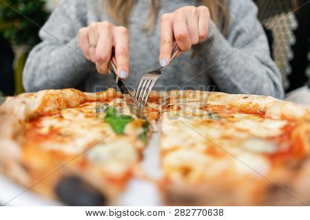 Woman Eats With Knife And Fork A Pizza Margherita With Mozzarella Tomatoes And Basil. Neapolitan Piz