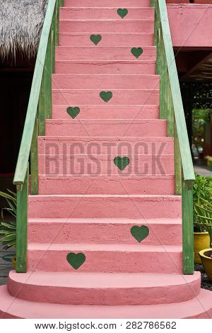 Colorful Pink Stair With Green Wooden Handrails Outdoors