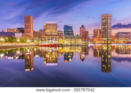 Baltimore, Maryland, USA Skyline on the Inner Harbor with dramatic skies at dusk.