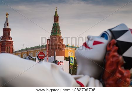 Statue Of A Clown On The Background Of The Corner Arsenal Tower Of The Kremlin. Holiday On The Occas
