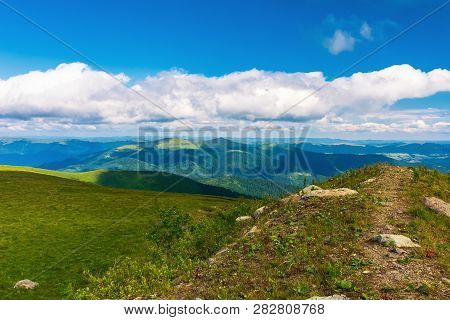 Beautiful Landscape In Mountains. Path Along The Hill. Grassy Meadow. Sunny Weather. Fluffy Clouds O