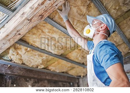 Old Roof Insulation. Caucasian Construction Worker In His 30s Inspecting Aged Roof And Mineral Wool