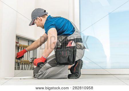 Residential Floor Heating Pipeline Box. Caucasian Plumbing Technician Checking On Pipes Valves.