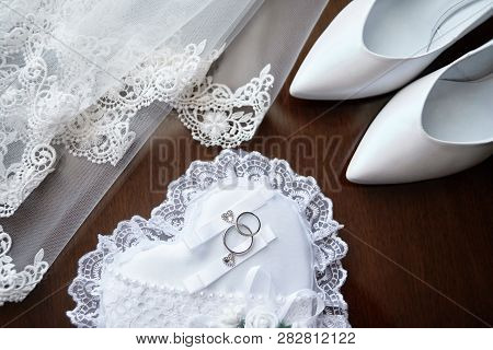 Luxury White Bride's Shoes On High Heels, Veil And Two Silver Wedding Rings On Wooden Background, Co