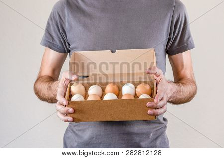 Caucasian Man With Gray T-shirt Holding A Cardboard Egg Box Full Of Hen Eggs On A White Background.