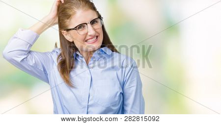 Beautiful middle age mature business woman wearing glasses over isolated background confuse and wonder about question. Uncertain with doubt, thinking with hand on head. Pensive concept.