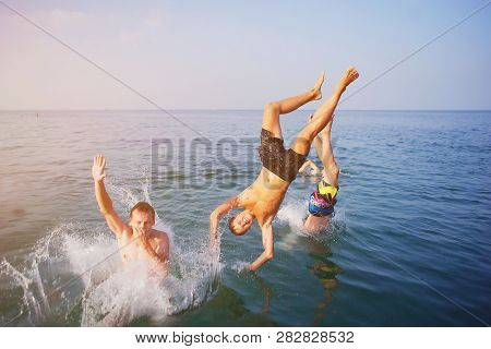 Young People Jumping Inside Ocean In Summer Excursion Day. Happy Crazy Friends Diving From Sailing B