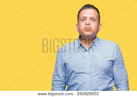 Middle age arab business man over isolated background puffing cheeks with funny face. Mouth inflated with air, crazy expression.