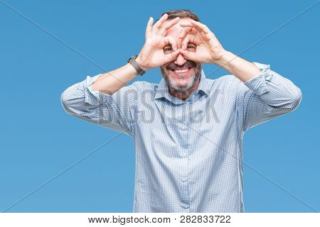 Middle age hoary senior business man over isolated background doing ok gesture like binoculars sticking tongue out, eyes looking through fingers. Crazy expression.
