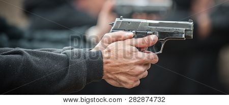 Detail view of shooter in row group of people hold gun and shooting on the shooting range poster