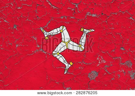 Flag Of Isle Of Man Painted On Cracked Dirty Wall. National Pattern On Vintage Style Surface.