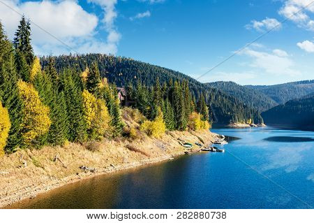 Mountain Lake Reservoir In Autumn. Hills With Coniferous Trees In The Distance. Beautiful Nature Sce