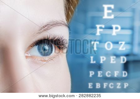 A Closeup Of A Female Grey Eye Looking Away And A Sight Test Table At Blurred Medical Room Backgroun
