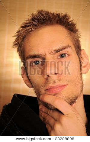 A portrait of a young Caucasian male in his early 20s thinking while scratching his chin poster