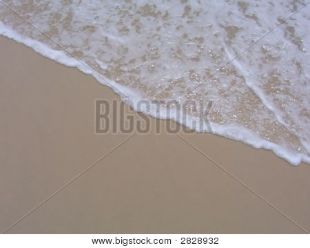Soft foam of a wave retreating from the sandy beach poster