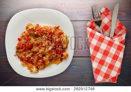 Stewed Tomatoes With Onions In A Plate On A Wooden Background. Stewed Tomatoes With Onion Top View.