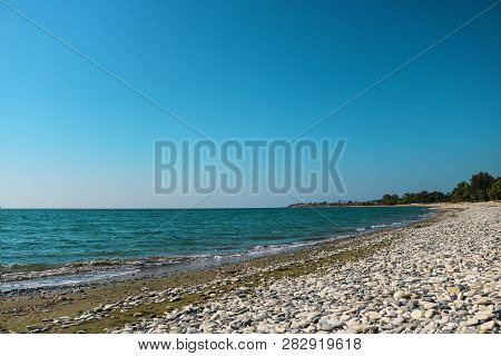 Empty Sea Shore With White Pebble, Landscape Sand And Round Sones On The Shore, Trees Far Away, Sea