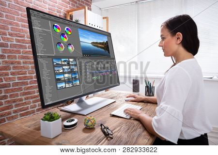 Side View Of Creative Female Editor Editing Video On Computer Over Wooden Desk