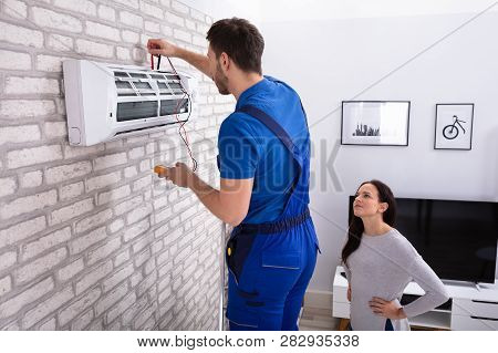 Smiling Woman Looking At Male Technician Repairing Air Conditioner With Digital Multimeter At Home