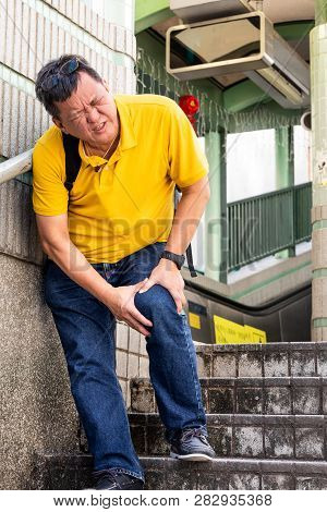 Man With Painful Knee Struggle Walking Down Flight Of Stairs