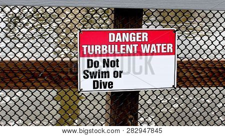 Danger Turbulent Water, Do Not Swin Or Dive Red And White Metal Sign On A Metal Fence Near A River.