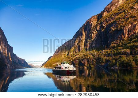 Ferry crossing calm Lysefjord (Lysefjorden) arriving to Lysebotn village at the end of the fjord in Forsand municipality of Rogaland county, Norway, Scandinavia