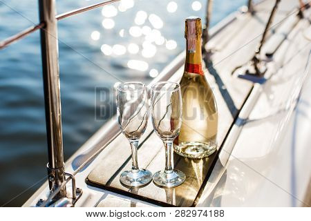 Romantic Luxury Evening On Cruise Yacht With Champagne Setting. Empty Glasses And Bottle With Champa