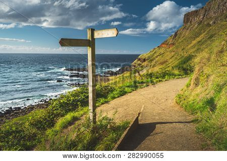 Close-up crossroad signpost. Northern Ireland shoreline. The hiking trail next to the Irish shore. Grass covered hill over the ocean. The wooden road sign on the tourist path. Stunning landscape.