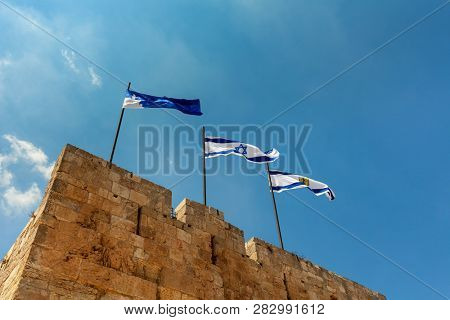 Flags of Israel and of Jerusalem waving on top of the Citadel walls wich surrounding Tower of David in Israel.