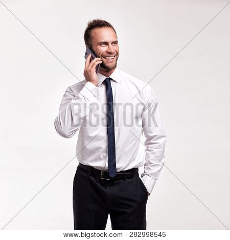 Portrait Of Young Handsome Smiling Businessman Speaking To Cellphone Isolated On White Studio Backgr