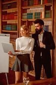 Reading concept. Sensual woman and handsome hipster reading ebook in library. Students update online reading material. Pretty girl and bearded man with laptop in reading room. poster
