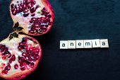 Cut pomegranate on a black background. Concept anemia and healthcare poster