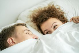 Top View Funny Caucasian Married Couple Lying On Bed And Hide Half Face