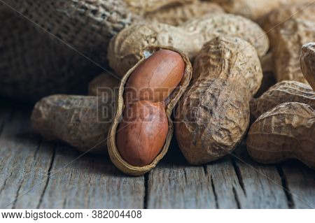Peanut In Nutshell On Rustic Table In Bowl Or Burlap Sack. Composition Of Peanuts Serving To Make Oi