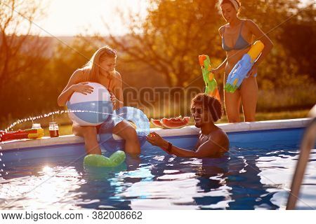 Friends having fun with water guns in pool.Happy young people   enjoy on summer holiday in swimming pool.
