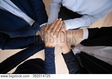 Corporate Staff Stacking Palms Together On Teambuilding Training