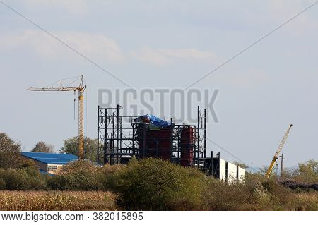 Metal Frame Of Large Industrial Hangar Under Construction At Local Industrial Complex Surrounded Wit