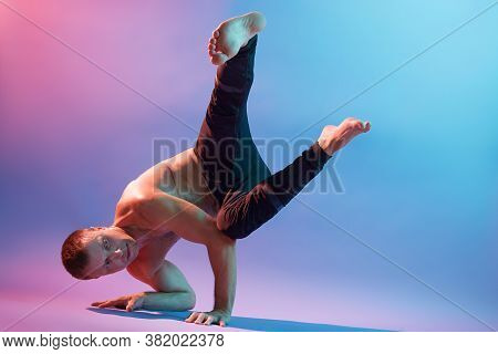 Strong Flexible Man Doing Morning Yoga Exercises Isolated Over Neon Wall, Wearing Black Pants, Looks