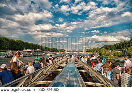 Paris, France - June 01, 2017: Seine River Cruise. People Travel By Riverboat On Cloudy Sky. Watersi