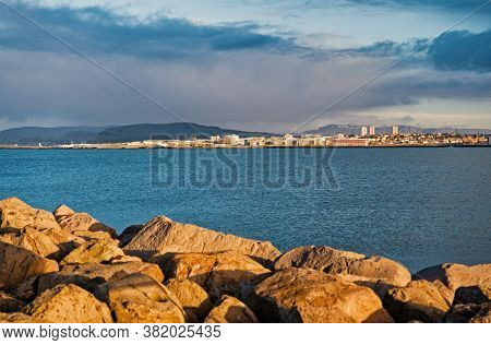 Coastal Defence And Fortification. Stony Breakwater In Sea. Breakwater Surround Docks, Ports And Lag