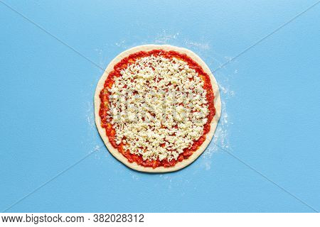 Pizza Making Of Above View On A Blue Colored Table. Pizza Dough With Tomato Sauce And Mozzarella Top