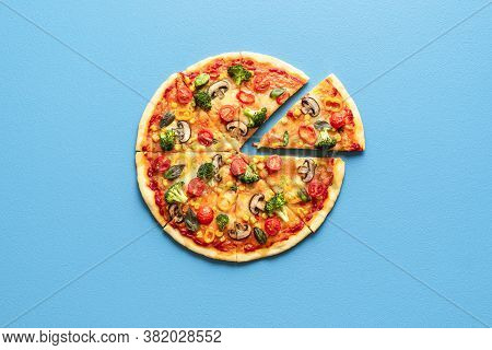 Vegetarian Pizza Isolated On A Blue Colored Background. Sliced Pizza Top View On Blue Table. Pizza W