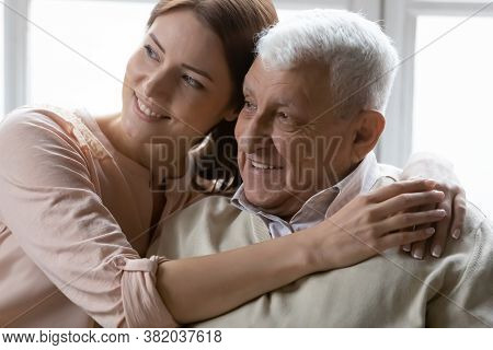 Affectionate Young Woman Cuddling Loving Positive Older Retired Daddy.