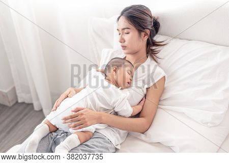 Being Mom Is So Exhausted.  Tired Mother Laid In Bed With Newborn Baby At Night. Authentic Real Life