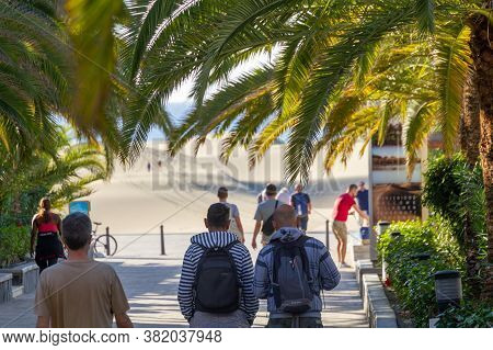 Playa Del Ingles, Spain - 5 Jan, 2020: Tourists Are Walking Toward Famous Maspalomas Dunes Beneath T